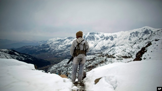 FILE - A Pakistani Army soldier with the 20th Lancers Armored Regiment stands atop the 8000-foot mountain during a patrol near his outpost, Kalpani Base, in Pakistan's Dir province on the Pakistan-Afghan border.