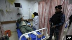 A police officer stands guard near his wounded comrade after a bomb attack, at a hospital in Baghdad, February 19, 2012.