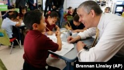 Education Secretary Arne Duncan visits with young student Mario Corona, age 6, in kindergarten at McGlone Elementary School in the Montbello section of Denver, in this May 14, 2015.