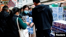 A customer holds toilet paper at a market, following the outbreak of a new coronavirus, in Hong Kong, China February 8, 2020.