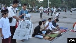 A family lays out a newspaper to be seated for morning prayer. (K. Varagur/VOA)