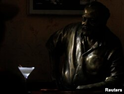 FILE - A Daiquiri is seen on the counter beside a life-size bronze statue of United States writer Ernest Hemingway at his regular spot at The Floridita bar in Havana, July 1, 2010.