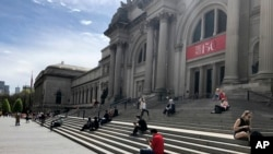 Des gens sont assis devant le Metropolitan Museum of Art le samedi 2 mai 2020 à New York, en respectant la distanciation sociale afin de prévenir la propagation du coronavirus. (Photo AP / Ron Blum)