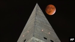 FILE - The supermoon passes behind the top of Washington Monument during a lunar eclipse on Sept. 27, 2015. People in many parts of North and South America will be able to see a total lunar eclipse Sunday night, Jan. 20, 2019 and early Monday morning.
