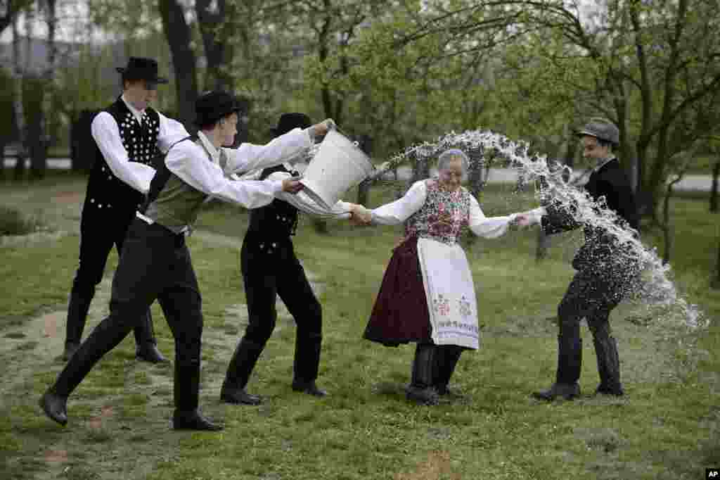Young men dressed in traditional Paloc folk costumes pour water from a bucket on a young woman performing a folk tradition, the Easter sprinkling, in Kazar, some 100 kilometers northeast of Budapest, Hungary, Good Friday, April 18, 2014.