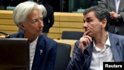 Direktur IMF Christine Lagarde (kiri) berbicara dengan Menteri Keuangan Yunani Euclid Tsakalotos dalam pertemuan menteri-menteri keuangan zona euro tentang situasi Yunani di Brussels, Belgia, 12 Juli 2015.