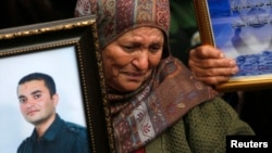 "A Palestinian woman holds a picture of a jailed relative during a protest marking ""Palestinian Prisoners Day"" in the West Bank city of Ramallah, April 17, 2013."