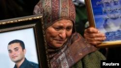 拉马拉的巴勒斯坦妇女在示威中拿着她被监禁的亲戚的图像