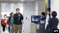 台湾疾病控制中心使用人体检测仪在桃园机场检测从武汉飞抵台北旅客的体温。(2020年1月13日)