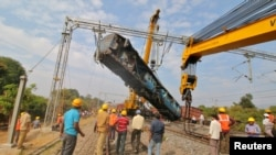 A damaged coach of a passenger train is removed after it derailed near Kuneru village in Vizianagaram district, in the southern state of Andhra Pradesh, India, Jan. 22, 2017.