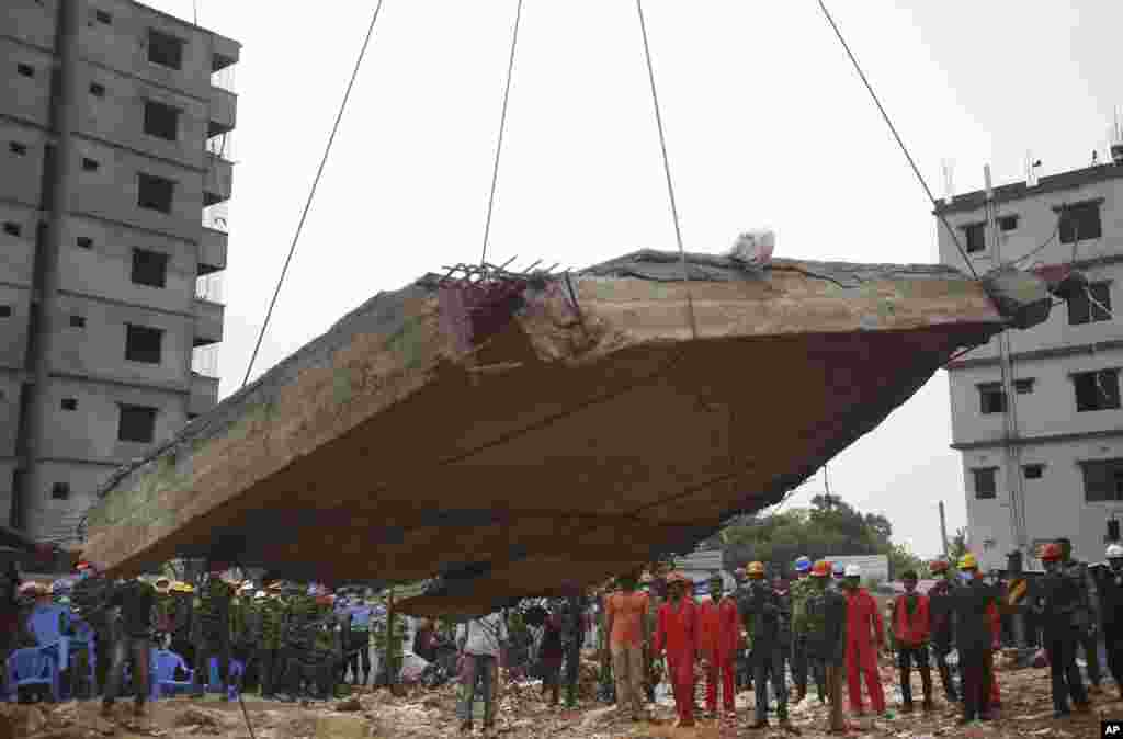Workers watch as a crane lowers the ceiling of the garment factory building which collapsed in Savar, near Dhaka, Bangladesh, April 29, 2013.