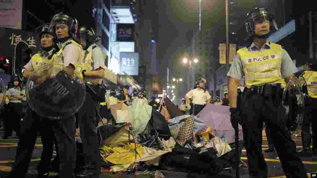Riot police stand guard next to broken umbrellas used by protesters to protect themselves at a pro-democracy protest encampment in the Mong Kok district of Hong Kong, Oct. 19, 2014.
