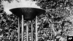Paavo Nurmi enciende la antorcha olímpica.