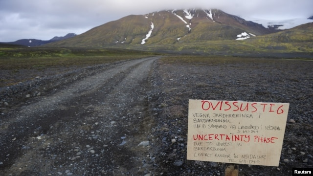 FILE - A warning sign blocks the road to Bardarbunga volcano, some 20 kilometers (12.5 miles) away, in the north-west region of the Vatnajokull glacier, Iceland, Aug. 19, 2014.