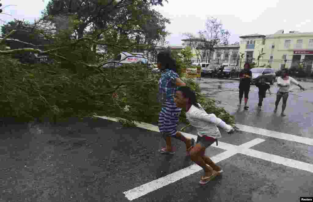 Residents rush to safety past a fallen tree during strong winds brought by Typhoon Haiyan that hit Cebu city, central Philippines, Nov. 8, 2013.