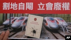 """FILE - An activist holds a card at a protest near the West Kowloon terminus of the Guangzhou-Shenzhen-Hong Kong Express Rail Link, Dec. 28, 2017. Some Hong Kong legal scholars say the """"co-location arrangement,"""" is unconstitutional."""