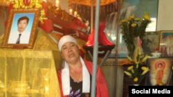 Chị Huỳnh Thị Muội bên cạnh quan tài của chồng, anh Nguyễn Hữu Tấn. Ảnh chụp từ Youtube 108TV Channel