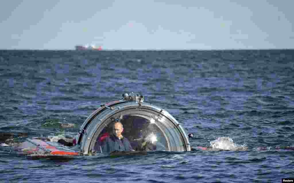 "Russia's President Vladimir Putin (L) is seen through the glass of C-Explorer 5 submersible after a dive to see the remains of the naval frigate ""Oleg&quot,; which sank in the 19th century, in the Gulf of Finland in the Baltic Sea."