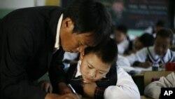 Seorang guru membantu seorang anak lelaki ketika dia menulis karakter-karakter Tibet selama kelas bahasa Tibet di Lhasa. (Foto: AP)