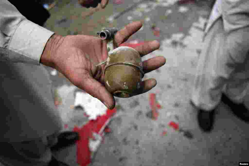A security official shows a grenade found at the site of a bomb attack in Quetta, Pakistan, April 24, 2013.
