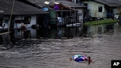 Children with a float swim through a swollen canal in Bangkok, Thailand, October 28, 2011.