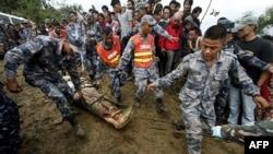 Nhân viên cứu hộ Nepal khiêng xác một nạn nhân ra khỏi đống đổ nát của chiếc máy bay Buddha Air bị lâm nạn ở vùng núi bên ngoài làng Bisankunarayan, phía nam thủ đô Katmandu, Nepal, ngày 25/9/2011