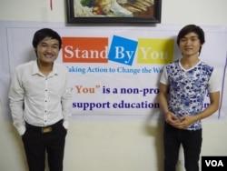 Phạm Minh Đáp (trái) và em trai đứng trước một tấm băng rôn quảng cáo lớp học ngoại ngữ miễn phí Stand By You cho học sinh, sinh viên nghèo (Marianne Brown/VOA)