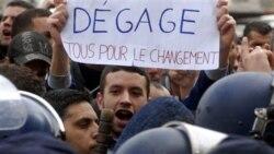 یک معترض الجزیره ای در برابر پلیش ضد شورش با تابلویی که بر روی آن نوشته شده: «برو بیرون، همه چیز برای تغییر»