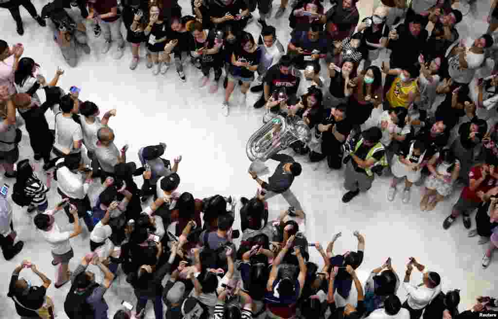 A man holds up a tuba as protesters shout slogans and sing Hong Kong's anthem during a protest at New Town Plaza shopping mall in Hong Kong, China.