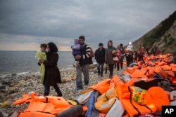 FILE - Refugees and migrants walk along a beach after crossing a part of the Aegean on a dinghy, from Turkey to the Greek island of Lesbos, Dec. 12, 2015.