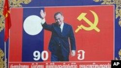 នៅក្នុងរូបថតថ្ងៃទី១៥ខែមិនាឆ្នាំ២០១១នេះ ពលរដ្ឋម្នាក់បើកម៉ូតូកាត់ពីមុខផ្ទាំងប៉ាណូមួយមានរូបអតីតមេដឹកនាំឡាវ Kaysone Phomvihane ក្នុងឱកាសប្រារព្ធសមាជលើកទី៩របស់គណបក្សបដិវត្តន៍ប្រជាជនឡាវ (Lao People's Revolutionary Party