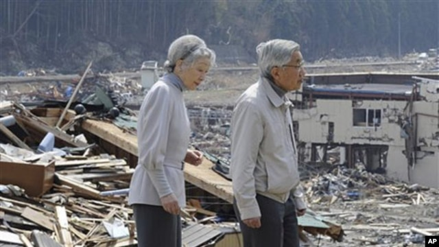 Japanese Emperor Akihito and Empress Michiko look at the tsunami-hit devastated area from the playground of Isatomae Elementary School in Minamisanriku, Miyagi Prefecture, northern Japan, April 27, 2011