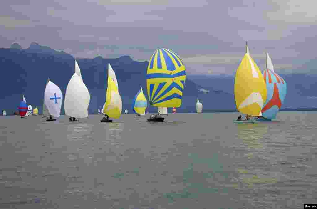 Wooden sailing boats take part in an exhibition regatta on Lake Leman near La Tour-de-Peilz, Switzerland, July 26, 2014.