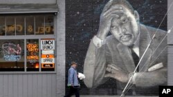 A man walks past a large mural of the Rev. Martin Luther King Jr. on the side of a diner, painted by artist James Crespinel in the 1990's and later restored, along Martin Luther King Jr. Way, Tuesday, April 3, 2018, in Seattle.