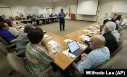 In this, Wednesday, Feb. 12, 2020 photo, Vincent Keeys, standing, president of the NAACP in Collier County, talks to a group of nonprofit leaders and government agencies about the Census undercount in 2010, in Immokalee, Florida.