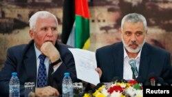 Pemimpin Hamas Ismail Haniyeh menunjukkan kesepakatan rekonsiliasi didampingi pejabat Fatah Azzam Al-Ahmed (kiri) di Gaza City, Rabu (23/4).
