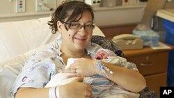 En esta foto propocionada por la Universidad de Colorado, Katie Medley carga a su recién nacido Hugo Jackson Medly, que junto a su padre, es sobreviviente de la masacre de los cines en Colorado.
