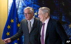 FILE - EU commission President Jean-Claude Juncker, left, welcomes George Soros, Founder and Chairman of the Open Society Foundation, prior to a meeting at EU headquarters in Brussels on Thursday, April 27, 2017.