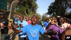 Wani mai goyn bayan 'yan hamayya dauke da adda a unguwar talakawa da ake kira Kawangware dake birnin Nairobi.