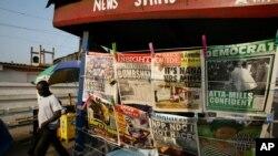 Un homme passe devant un kiosque à journaux près de la station de Neoplan à Accra, au Ghana, 8 décembre 2008.