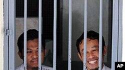 Rohmat Puji Prabowo (alias Bejo) (L) and Supono (alias Kedu) wait inside a cell at the South Jakarta court in Jakarta, 22 Jun 2010