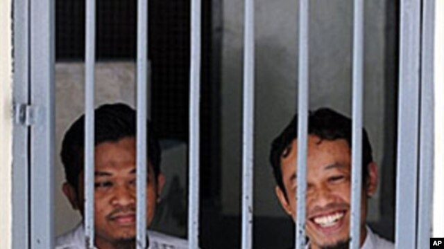 Rohmat Puji Prabowo (alias Bejo) (L) and Supono (alias Kedu) wait inside a cell at the South Jakarta court in Jakarta, 22 Jun 2010