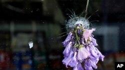 Una flor colocada en uno de los hoyos de la tienda de conveniencia donde murió una persona.