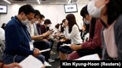 Para peserta acara perjodohan di Tokyo memakai masker saat berkomunikasi satu sama lain (16/10). (Reuters/Kim Kyung-Hoon)