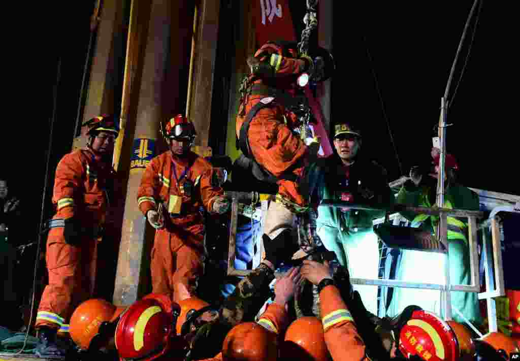 The first miner, is lifted from a collapsed mine in Pingyi, east China's Shandong Province. Chinese state media say two miners have been rescued from a collapsed mine after spending 36 days trapped underground. The gypsum mine collapsed on Christmas Day, killing one and leaving 13 others missing.