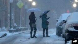 15일 미국 북동부 보스턴 눈 내리는 거리에서 사람들이 우산을 쓰고 걸어가고 있다.