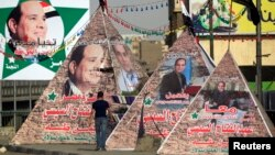 A man walks near replicas of Giza Pyramid covered with banners of presidential candidate and former army chief Abdel Fattah al-Sissi in Cairo, May 26, 2014.