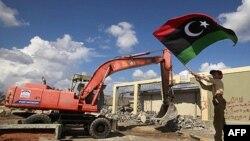 Máy ủi đất kéo đổ những bức tường chung quanh khu tổng hành dinh Bab al-Aziziyah của ông Gadhafi, 16/10/2011
