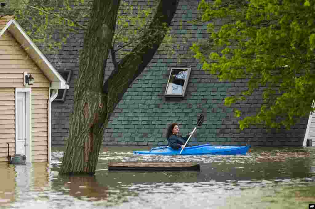 A woman use a kayak to examine the damage at homes in her neighborhood on Oakridge Road on Wixom Lake in Beaverton, Michigan. Quickly rising water has overtaken dams and forced the about 10,000 people from their homes in central Michigan. (Credit: Midland Daily News)