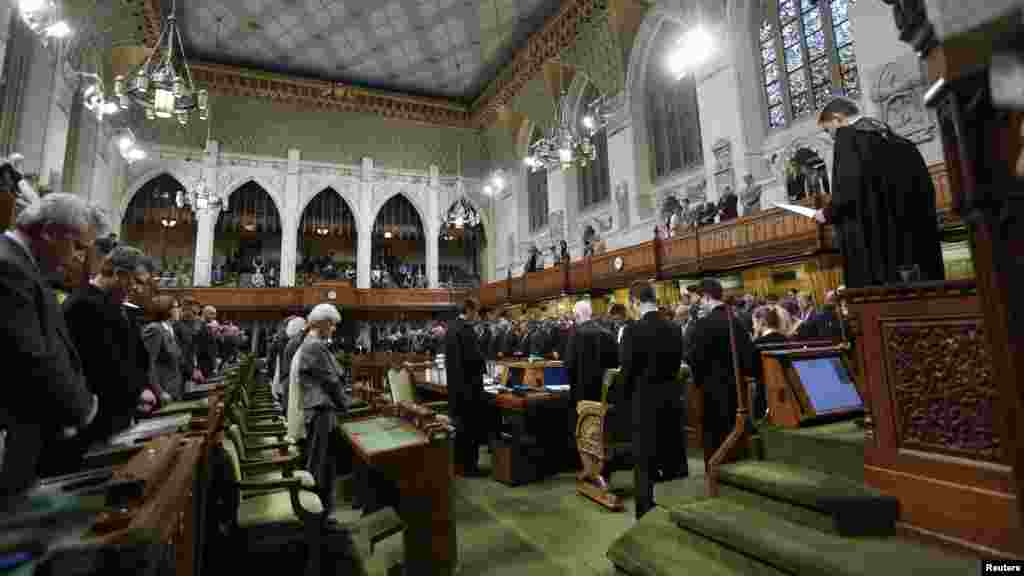 Canada's Members of Parliament stand in the chamber of the House of Commons in Ottawa, Oct. 23, 2014.